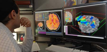 Scientist looking at brainscans on computer screens