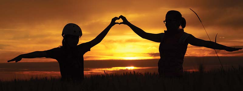 two persons forming heart shape with hands